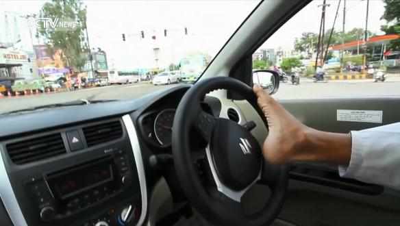 بالفيديو – رجل مبتور الذراعين يقود سيارته بقدميه