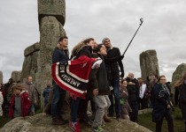 AMESBURY, ENGLAND - DECEMBER 22:  People gather to take a selfie photograph as pagans and revellers gather at Stonehenge, hoping to see the sun rise, as they take part in a winter solstice ceremony at the ancient neolithic monument of Stonehenge near Amesbury on December 22, 2015 in Wiltshire, England. Despite a forecast for rain, a large crowd gathered at the famous historic stone circle, a UNESCO listed ancient monument, to celebrate the sunrise closest to the Winter Solstice, the shortest day of the year. The event is claimed to be more important in the pagan calendar than the summer solstice, because it marks the 're-birth' of the Sun for the New Year.  (Photo by Matt Cardy/Getty Images)