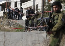 An Israeli security forces member stands guard as his comrades gather around the body of a Palestinian man who rammed his car into Israeli soldiers injuring five of them before being shot dead, in the village of Beit Ummar, near the city of Hebron in the Israeli occupied West Bank, on November 27, 2015. The soldiers were lightly injured in the incident near the flashpoint city of Hebron, according to the Israeli emergency services. AFP PHOTO / HAZEM BADER / AFP / HAZEM BADER        (Photo credit should read HAZEM BADER/AFP/Getty Images)