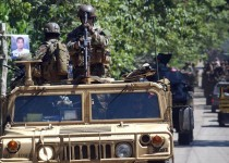 A fully armed soldier from the elite US Special Forces mans a machine gun mounted on a US military humvee jeep seen on a convoy with Philippine Marine troops along the road in Indanan town in the restive southern Philippine island of Jolo 14 August 2007.  12,000 Filipino combat troops backed by helicopter gunship fanned out across Jolo and nearby Basilan island as part of an offensive against Islamic militants , officials said. Government forces are hunting members of the Al-Qaida linked Abu Sayyaf group responsible for some of the country's worst terrorist attacks. Last week's clash in Jolo left 26 soldiers dead while 14 marines died in July clash in Basilan. A small number of US military advisers and troops are in Jolo providing intelligence assistance to Philippine forces. AFP PHOTO/THERENCE KOH (Photo credit should read THERENCE KOH/AFP/Getty Images)