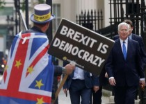 Britain's Conservative Party lawmaker Michael Fallon arrives passing a demonstrator, to attend the launch of Boris Johnson's leadership campaign, in London, Wednesday June 12, 2019. Boris Johnson solidified his front-runner status in the race to become Britain's next prime minister on Tuesday, gaining backing from leading pro-Brexit lawmakers.(AP Photo/Kirsty Wigglesworth)